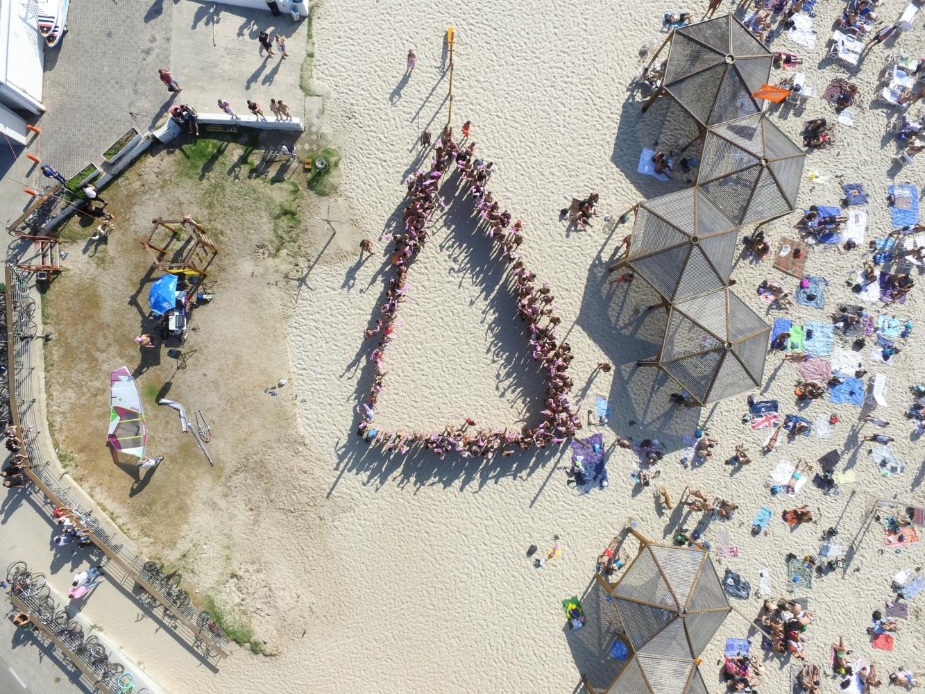 Beachgoers form a pink triangle at the Hilton Beach to show their support for the gay men in Chechnya.  The pink triangle was first used by Hitler to identify gay men during the Holocaust.