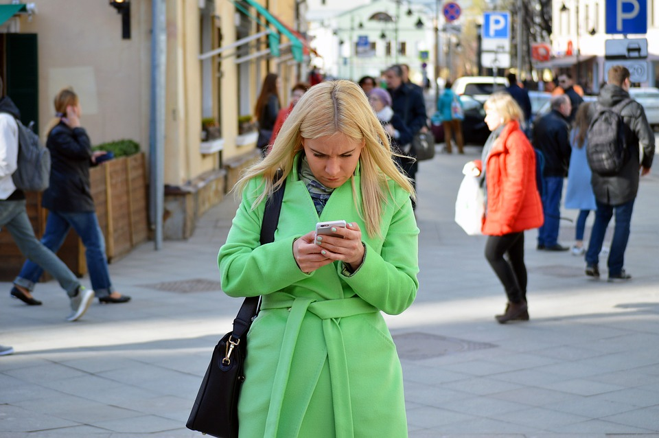 Many young adults simultaneously walk and text, never looking up from their phones.